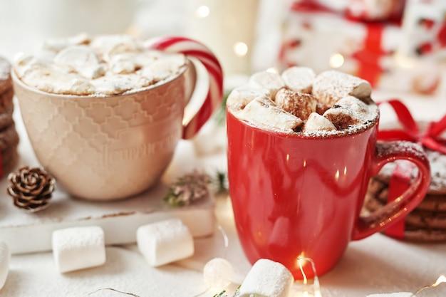 Biscoitos de natal, leite, cacau, marshmallows, doces em um prato branco perto da janela Foto Premium