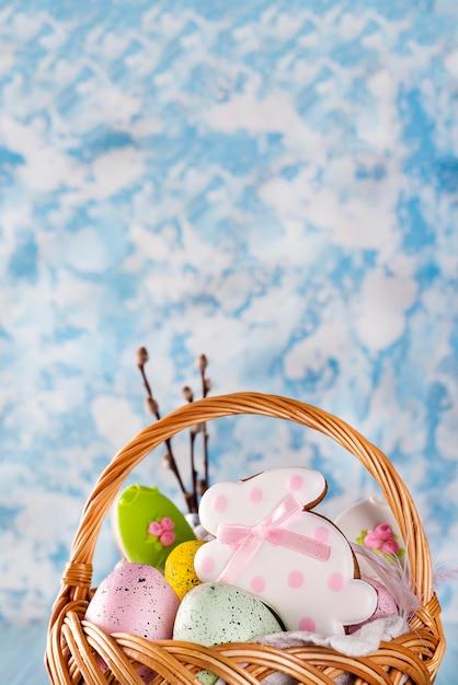 Biscoitos de páscoa, coelhinhos e ovos de páscoa coloridos em uma cesta na luz de fundo azul Foto Premium