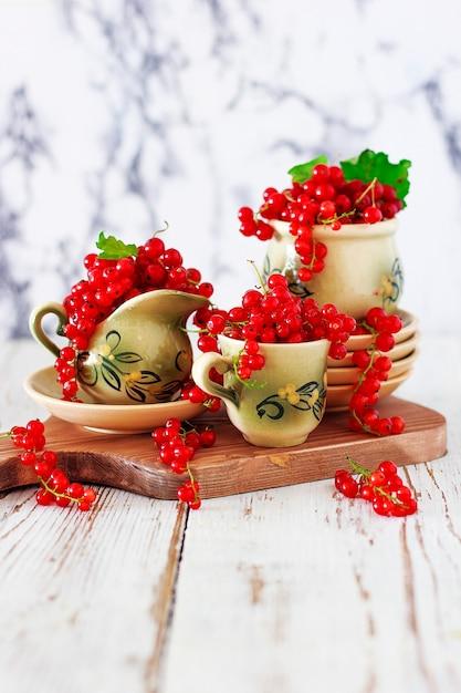 Biscoitos de queijo cottage com groselhas na placa cerâmica com conjunto de chá ou café em cerâmica vintage, hora do chá, café da manhã, doces de verão Foto gratuita