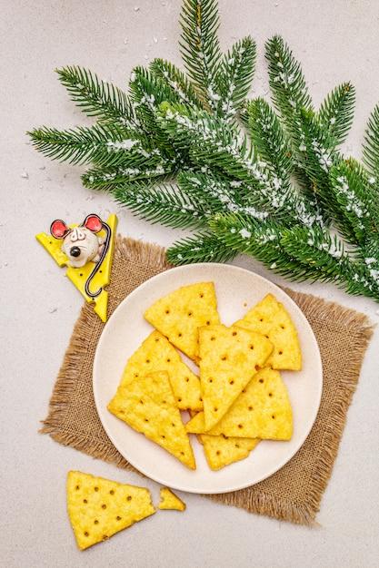 Biscoitos de queijo festivo, conceito de lanche do ano novo. biscoitos, figura de rato, galho de árvore do abeto, neve artificial, guardanapo de pano de saco. Foto Premium