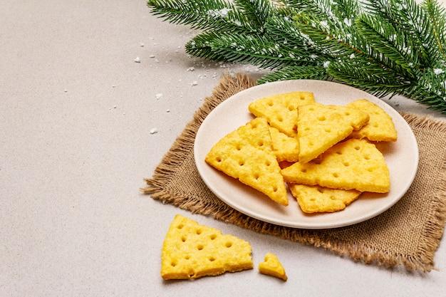 Biscoitos de queijo festivo, conceito de lanche do ano novo. biscoitos, galho de árvore do abeto, neve artificial, guardanapo de pano de saco. fundo de pedra concreto Foto Premium