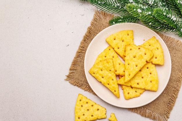 Biscoitos de queijo festivo, conceito de lanche do ano novo. biscoitos, galho de árvore do abeto, neve artificial, guardanapo de pano de saco. Foto Premium