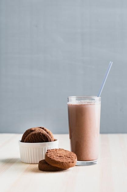 Biscoitos de vista frontal com leite com chocolate em copo com canudo Foto gratuita