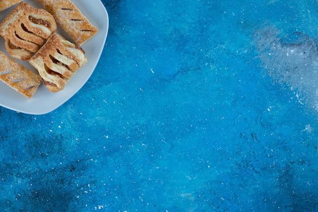 Biscoitos deliciosos com geléia no prato, no fundo azul. foto de alta qualidade Foto gratuita