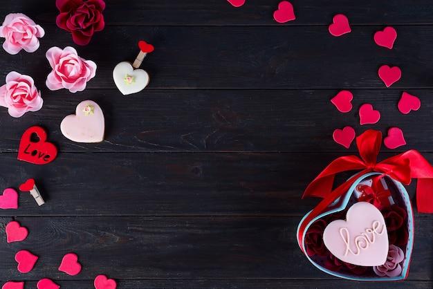 Biscoitos do dia dos namorados em forma de coração no fundo escuro de madeira Foto Premium