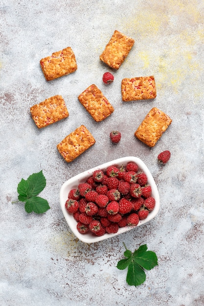 Biscoitos doces e deliciosos de geléia de framboesa com framboesas maduras, vista de cima Foto gratuita