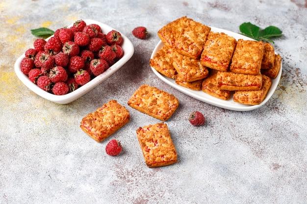 Biscoitos doces e deliciosos de geléia de framboesa com framboesas maduras, vista superior Foto gratuita
