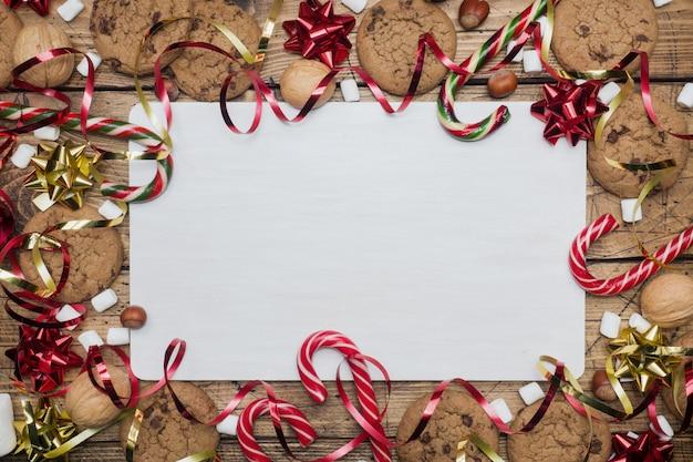 Biscoitos dos pedaços de chocolate cenário vermelho e marshmallow do ouro do caramelo dos bastões do natal em de madeira. quadro de copyspace. Foto Premium