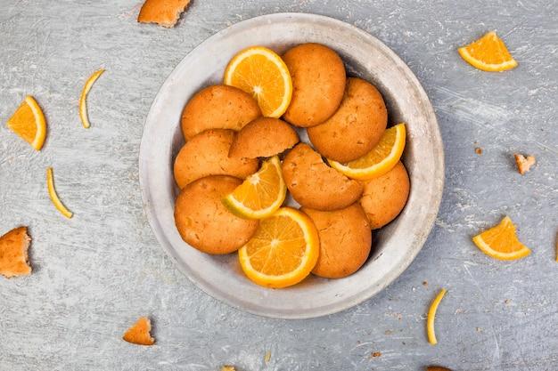 Biscoitos e frutas cítricas laranja na placa de metal no fundo cinza Foto Premium