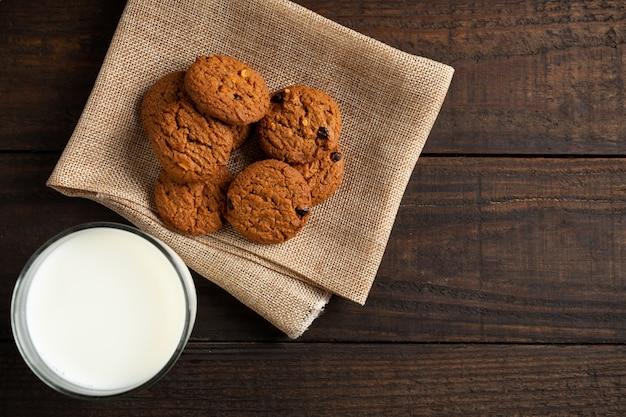 Biscoitos e leite de vidro na mesa de madeira. Foto gratuita
