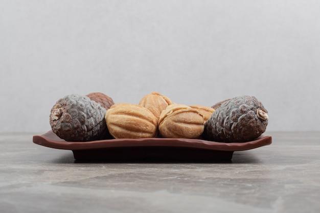 Biscoitos e pinhas em forma de noz na placa escura. Foto gratuita