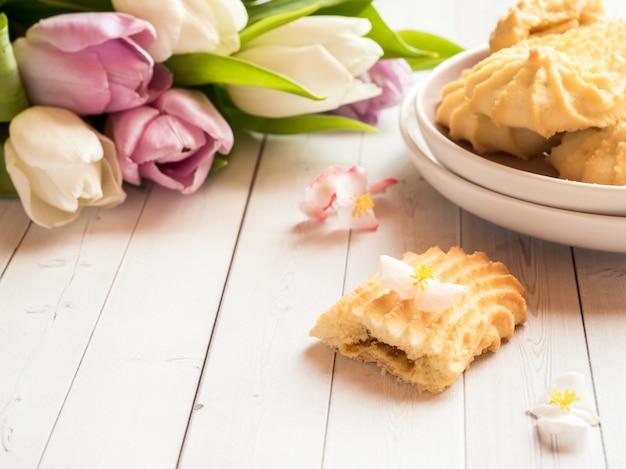 Biscoitos e tulipas em uma mesa de madeira. Foto Premium