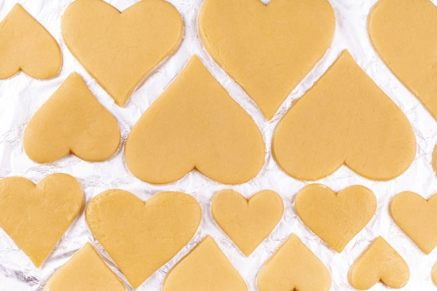 Biscoitos em forma de coração caseiro cru deite-se sobre papel alumínio e prepare-se para ser enviado ao forno Foto Premium