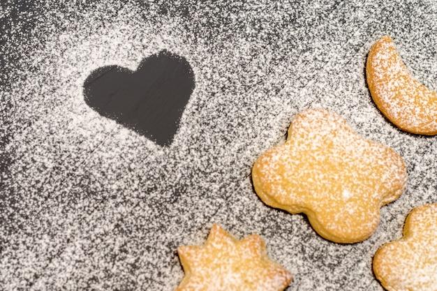 Biscoitos em forma de natal com açúcar em pó na mesa de madeira escura Foto Premium