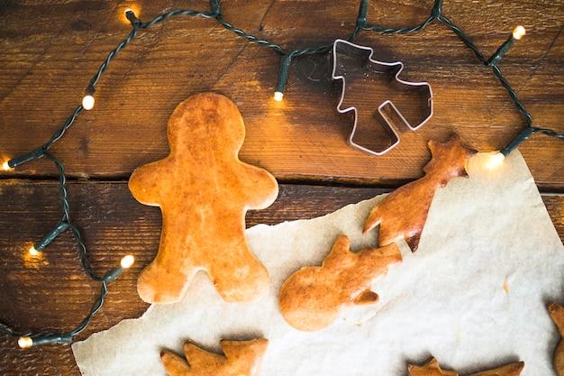 Biscoitos frescos perto de formulário para cookie e luzes de fada Foto gratuita