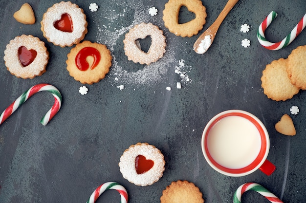 Biscoitos linzer tradicionais de natal com geléia de morango, bastões de doces e leite no escuro Foto Premium