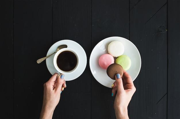 Biscoitos macaron, xícara de café expresso e mãos de ladie Foto Premium