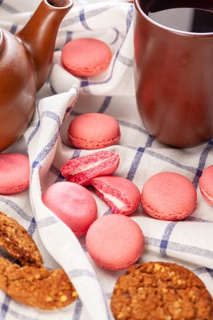 Biscoitos minúsculos rosa macaron numa toalha de mesa close-up Foto Premium