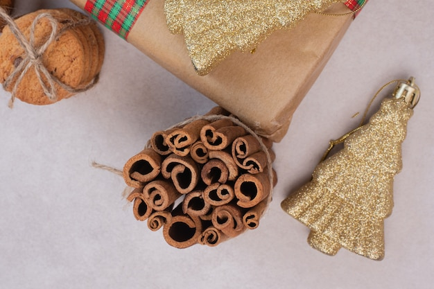 Biscoitos na corda com paus de canela e brinquedo de natal na superfície branca Foto gratuita