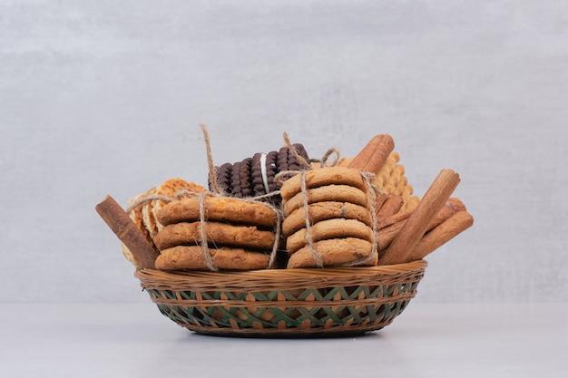 Biscoitos na corda com paus de canela na superfície branca Foto gratuita