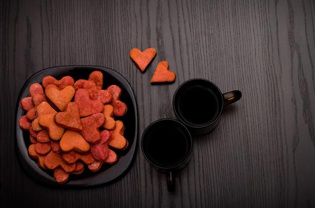 Biscoitos vermelhos em forma de coração em um prato preto, duas canecas de café, vista superior Foto Premium