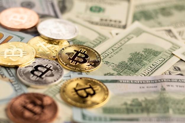 Bitcoin acima de notas de dólar close-up Foto gratuita