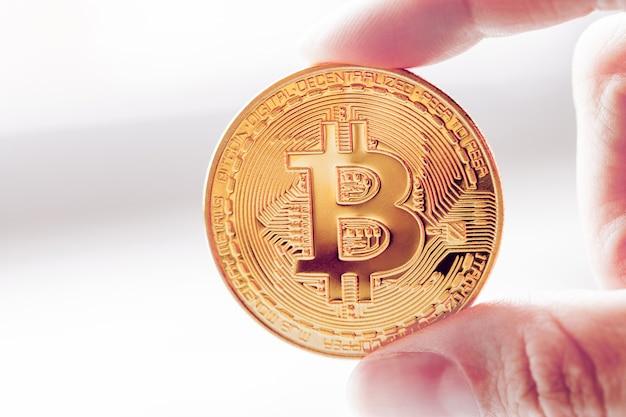 Bitcoin de ouro em uma mão Foto Premium