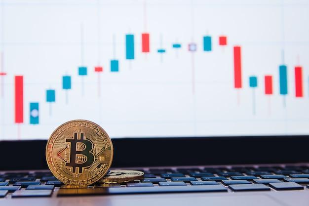 Bitcoin dourado no laptop teclado com gráfico de negociação forex Foto Premium