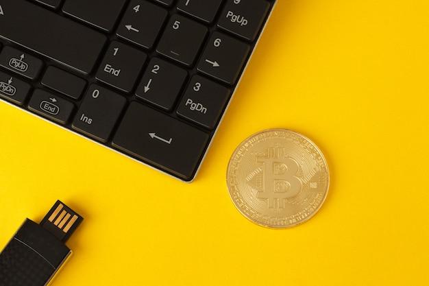 Bitcoin dourado, teclado e pen drive em um fundo amarelo Foto Premium