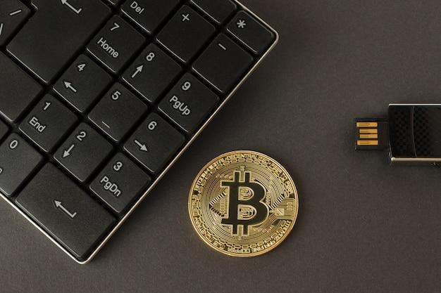 Bitcoin dourado, teclado e pen drive em uma vista superior de fundo escuro Foto Premium