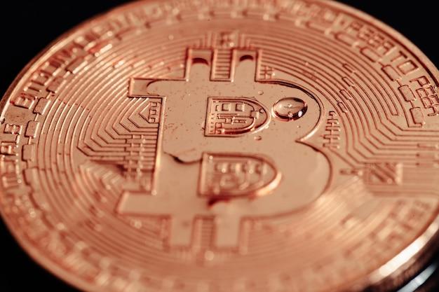 Bitcoin em fundo preto. a crise econômica mundial. bitcoin não é uma moeda estável. foto macro Foto Premium