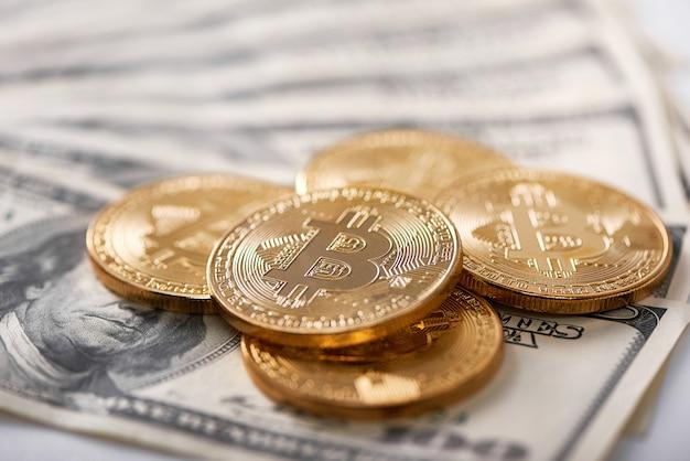 Bitcoins de ouro nas notas de dólar Foto Premium