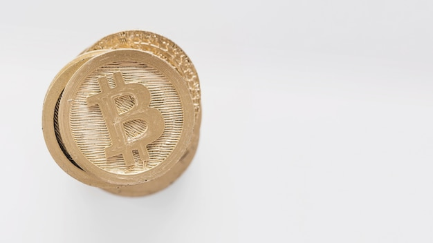 Bitcoins dourados empilhados no fundo branco Foto gratuita