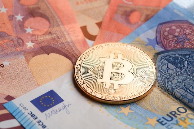 Bitcoins dourados empilhados no fundo das notas de euro. Foto Premium