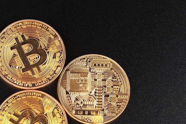 Bitcoins dourados sobre fundo preto. conceito de negociação de moeda criptografada Foto Premium