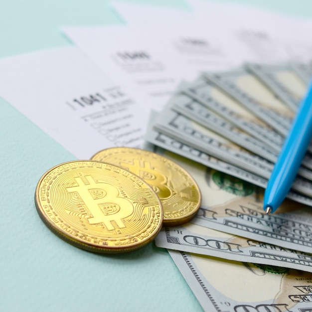 Bitcoins encontra-se com as formas de impostos e notas de cem dólares Foto Premium
