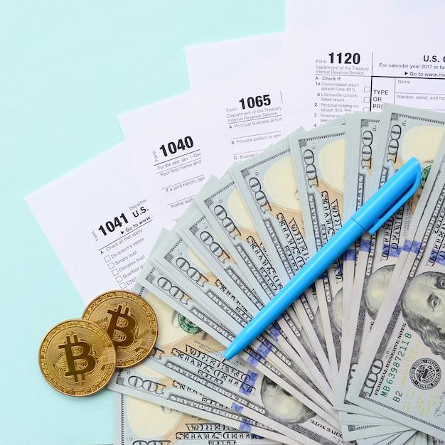Bitcoins encontra-se com os formulários de imposto e notas de cem dólares em um fundo azul claro. restituição do imposto de renda Foto Premium