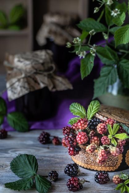 Blackberry berry em um galho com folhas em uma caixa de madeira esculpida em um escuro de madeira Foto Premium
