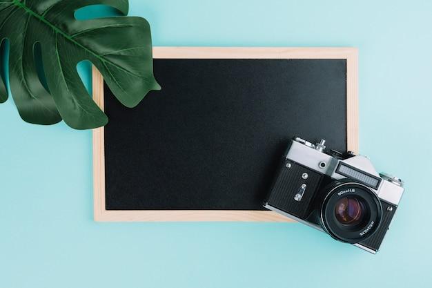 Blackboard com câmera e folha Foto gratuita