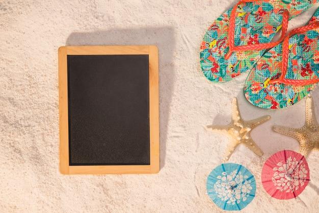 Blackboard flip-flops estrela do mar e guarda-sóis na areia Foto gratuita