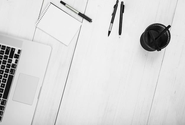 Bloco de anotações; canetas; suporte e laptop no pano de fundo de madeira branco Foto gratuita