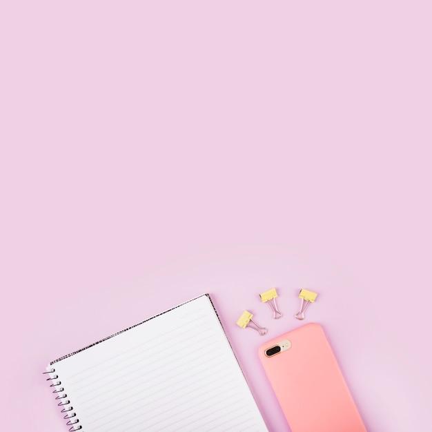 Bloco de anotações; clipes de buldogue e celular na superfície rosa Foto gratuita