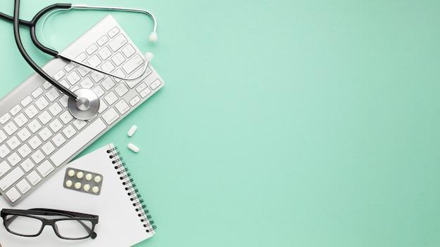 Bloco de anotações; teclado sem fio com estetoscópio e medicamentos sobre a superfície Foto gratuita