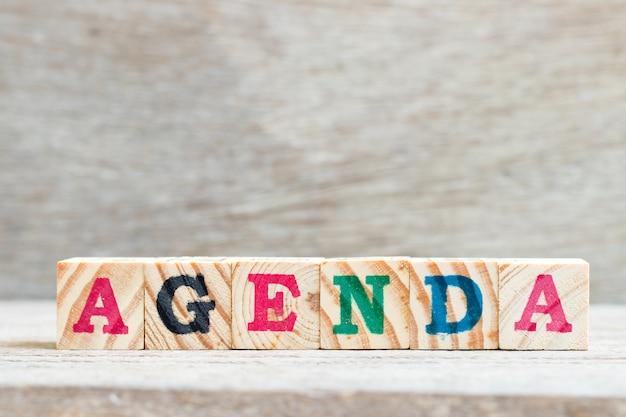 Bloco de carta na palavra agenda em fundo de madeira Foto Premium