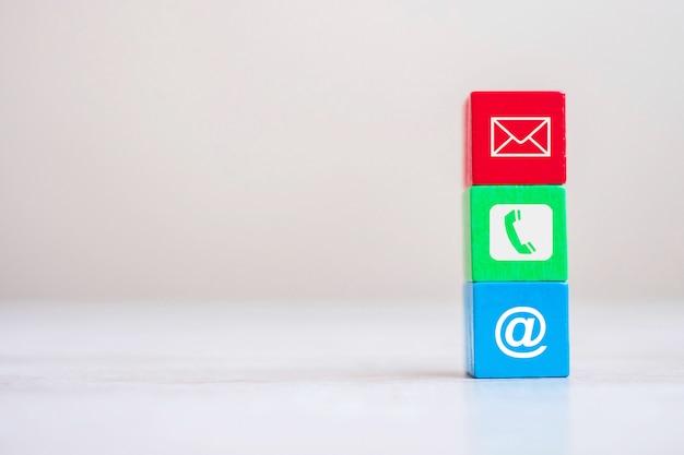 Bloco de cubo com símbolo de site, e-mail, telefone e endereço no fundo da tabela Foto Premium