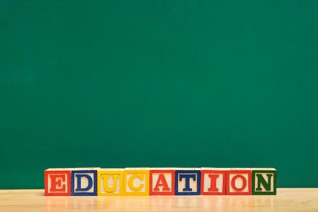 Bloco de madeira de palavra educação colorido na mesa de madeira com lousa verde Foto Premium