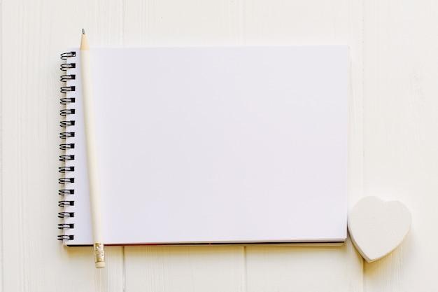 Bloco de notas aberto com página vazia para espaço de cópia com um lápis e coração de madeira branco Foto Premium