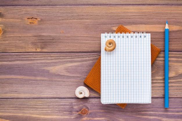 Bloco de notas aberto limpo para escrever, lápis, passaporte e concha do mar em madeira Foto Premium