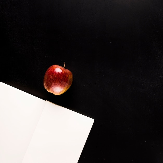 Bloco de notas com frutas na mesa preta Foto gratuita