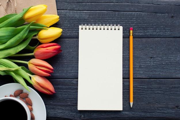 Bloco de notas com lápis ao lado das tulipas. Foto Premium